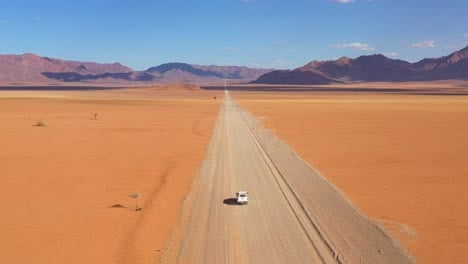 High-aerial-over-a-Toyota-safari-vehicle-heading-across-the-flat-barren-Namib-Desert-in-Namibia-6