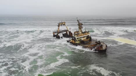 Dramatic-aerial-over-a-spooky-shipwreck-grounded-fishing-trawler-along-the-Skeleton-Coast-of-Namibia