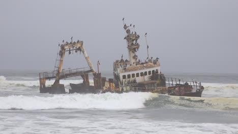A-spooky-shipwreck-grounded-fishing-trawler-sits-in-Atlantic-waves-along-the-Skeleton-Coast-of-Namibia