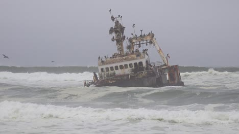 A-spooky-shipwreck-grounded-fishing-trawler-sits-in-Atlantic-waves-along-the-Skeleton-Coast-of-Namibia-1