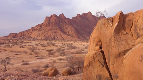 Massive-rock-formations-and-safari-vehicle-distant-at-Spitzkoppe-Namibia