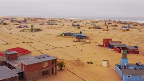 Aerial-over-a-strange-lonely-barren-post-apocalyptic-beach-side-settlement-of-summer-homes-at-Hengtiesbaai-Namibia