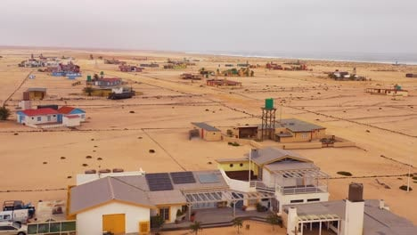 Aerial-over-a-strange-lonely-barren-post-apocalyptic-beach-side-settlement-of-summer-homes-at-Hengtiesbaai-Namibia-1
