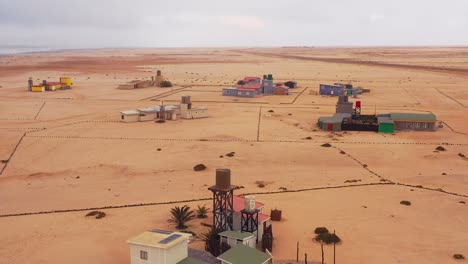 Aerial-over-a-strange-lonely-barren-post-apocalyptic-beach-side-settlement-of-summer-homes-at-Hengtiesbaai-Namibia-3