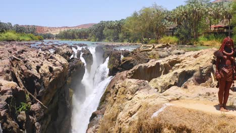 Aerial-reveals-two-Himba-tribal-women-girls-in-front-of-Epupa-waterfalls-on-the-Angola-Namibia-border-Africa