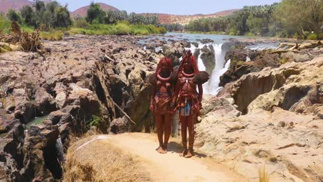 Aerial-reveals-two-Himba-tribal-women-girls-in-front-of-Epupa-waterfalls-on-the-Angola-Namibia-border-Africa-1