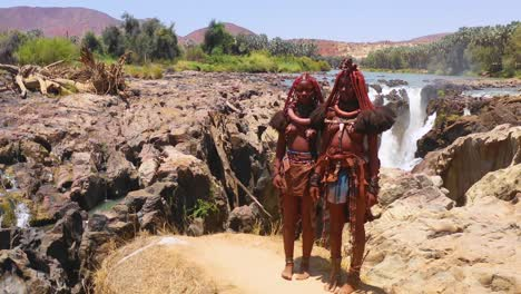 Aerial-reveals-two-Himba-tribal-women-girls-in-front-of-Epupa-waterfalls-on-the-Angola-Namibia-border-Africa-2