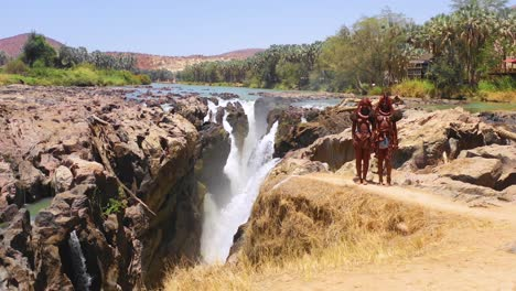 Aerial-reveals-two-Himba-tribal-women-girls-in-front-of-Epupa-waterfalls-on-the-Angola-Namibia-border-Africa-3