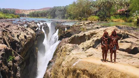 Aerial-reveals-two-Himba-tribal-women-girls-in-front-of-Epupa-waterfalls-on-the-Angola-Namibia-border-Africa-4