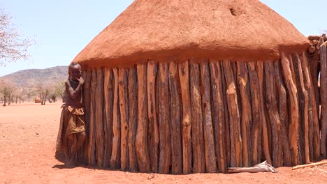 A-young-African-Himba-tribal-boy-leans-against-his-mud-and-wood-hut-in-a-small-village-in-Namibia-1