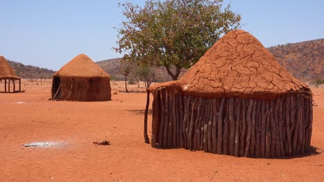 Small-poor-African-Himba-rural-village-on-the-Namibia-Angola-border-with-mud-huts-goats-and-children