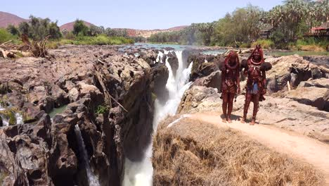 Two-Himba-tribal-women-in-full-costume-dance-and-laugh-at-Epupa-Falls-Namibia