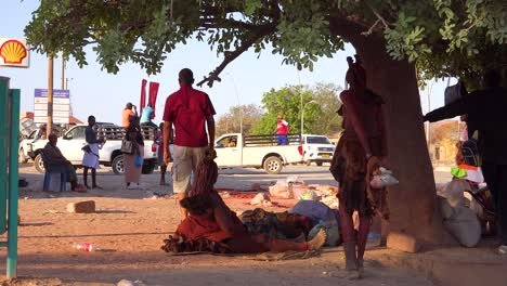 Native-Himba-tribal-men-and-women-stand-around-in-the-streets-of-Opuwo-Namibia-with-traffic-passing