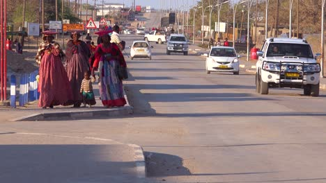 Opuwo-Namibia-market-town-street-and-traffic-with-shops-and-pedestrians-and-Herero-women-in-costume
