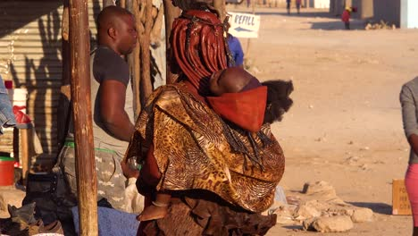 A-Himba-tribal-woman-with-baby-on-back-and-amazing-hairstyle-of-mud-and-braids-and-dreadlocks-in-the-market-town-of-Opuwo-Namibia