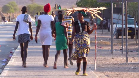 A-tribal-woman-walks-on-the-streets-of-a-market-town-in-Africa-Opuwo-Namibia-with-firewood-balanced-on-head