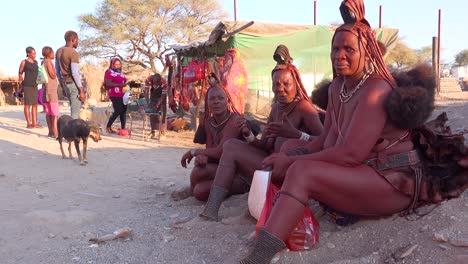 Three-Himba-tribal-women-sit-by-the-road-in-the-market-town-of-Opuwo-Namibia-with-amazing-braided-mud-soaked-and-dreadlock-hair-styles-1