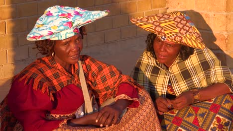 Two-Herero-tribal-women-in-large-flat-hats-and-dresses-in-a-market-town-of-Opuwo-Namibia-Africa