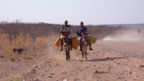 Two-Himba-men-ride-donkeys-along-a-dusty-road-in-Africa-Damaraland-Namibia-bringing-water-to-remote-villages