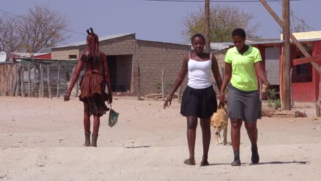 Modern-and-traditional-Himba-tribal-women-walk-on-a-street-in-a-small-village-in-Damaraland-Namibia