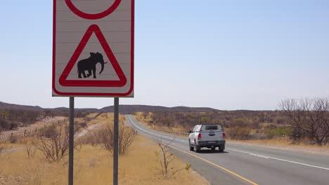Un-Signo-De-Cuidado-Con-El-Cruce-De-Elefantes-Con-Jeep-Pasando-Advierte-A-Los-Visitantes-En-Un-Camino-De-Tierra-En-Namibia-África