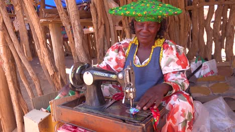 A-Herero-African-tribal-woman-in-bright-fashion-costumes-operates-an-antique-sewing-machine-in-a-marketplace-in-Namibia-Africa