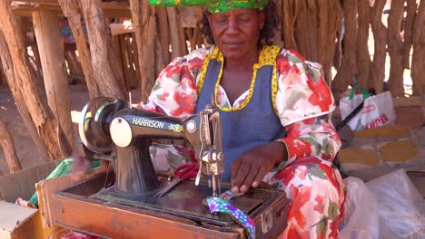 A-Herero-African-tribal-woman-in-bright-fashion-costumes-operates-an-antique-sewing-machine-in-a-marketplace-in-Namibia-Africa-1