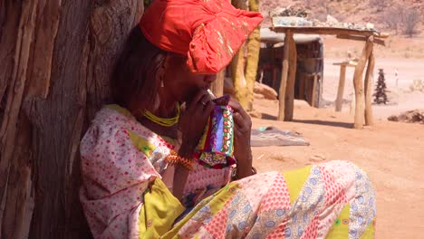 A-Herero-African-tribal-woman-in-bright-fashion-costumes-sews-by-hand-in-a-marketplace-in-Namibia-Africa