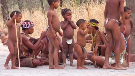 African-San-bushmen-women-niños-and-tribal-natives-sit-in-a-circle-chanting-singing-and-clapping-in-a-small-village-in-Namibia-2