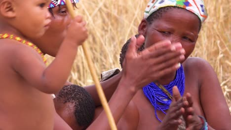 African-San-bushmen-women-children-and-tribal-natives-sit-in-a-circle-chanting-singing-and-clapping-in-a-small-village-in-Namibia-3