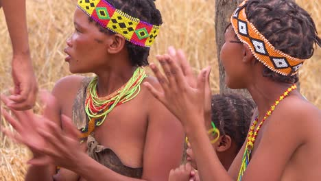 African-San-bushmen-women-children-and-tribal-natives-sit-in-a-circle-chanting-singing-and-clapping-in-a-small-village-in-Namibia-4
