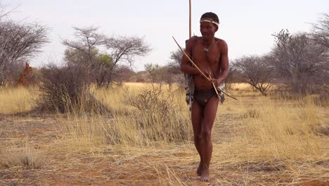 A-San-tribal-bushman-hunter-in-Namibia-Africa-walks-quiety-sniffs-the-air-and-samples-the-soil-for-wind-direction-hunting-for-prey-1