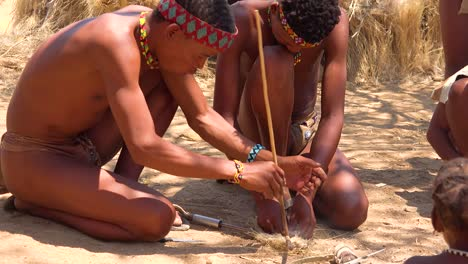 African-San-tribal-bushmen-make-fire-the-traditional-way-in-a-small-primitive-village-in-Namibia-Africa-1