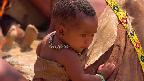 A-baby-looks-on-while-African-San-tribal-bushmen-perform-a-fire-dance-in-a-small-primitive-village-in-Namibia-Africa