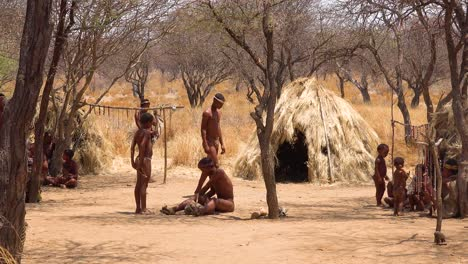 African-San-tribal-bushmen-family-at-their-huts-in-a-small-primitive-village-in-Namibia-Africa-3