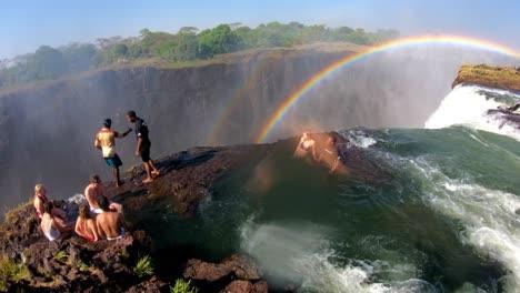 Los-Turistas-Se-Reúnen-En-La-Piscina-Del-Diablo-Al-Borde-De-Las-Cataratas-Victoria-Zambia-Para-Echar-Un-Vistazo-Al-Borde-De-Las-Cascadas