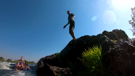 A-man-dives-into-Devil-s-Pool-the-edge-of-Victoria-Falls-Zambia-close-to-the-edge-of-the-waterfalls