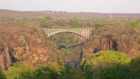A-steam-passenger-train-crosses-a-bridge-near-Victoria-Falls-Zimbawbwe-or-Zambia-Africa