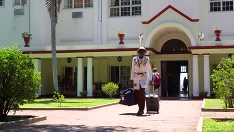 A-porter-or-bellman-in-colonial-outfit-brings-tourist-luggage-from-the-posh-and-elegant-Victoria-Falls-Hotel-in-Zimbawbwe