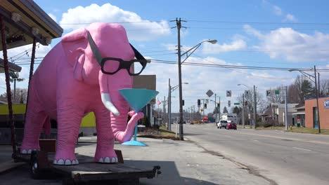 Un-Elefante-Rosa-Gigante-Se-Sienta-Junto-A-La-Carretera-Con-Un-Martini-En-Su-Trompa-En-Una-Pequeña-Ciudad-En-La-Zona-Rural-De-Fortville-Indiana