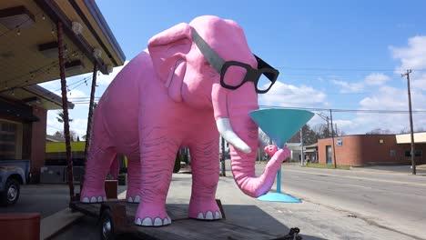 Un-Elefante-Rosa-Gigante-Se-Sienta-Al-Lado-De-La-Carretera-Con-Un-Martini-En-Su-Trompa-En-Una-Pequeña-Ciudad-En-La-Zona-Rural-De-Fortville-Indiana-1
