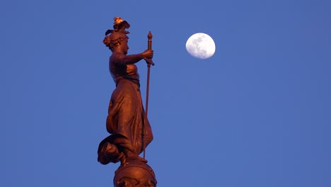 Statue-atop-Soldiers-and-Sailors-Monument-with-moon-rising-in-downtown-Indianapolis-Indiana
