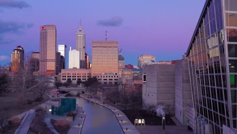 Nice-drone-aerial-of-downtown-Indianapolis-Indiana-at-dusk-or-night-with-riverwalk-foreground