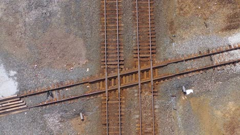 Aerial-looking-straight-down-over-a-railroad-track-intersection-with-a-freight-train-passing-underneath