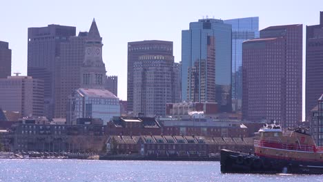 A-tugboat-moves-in-front-of-the-downtown-city-skyline-and-financial-district-of-Boston