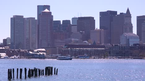 A-water-taxi-moves-in-front-of-the-downtown-city-skyline-and-financial-district-of-Boston-Massachusetts