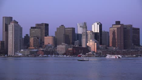 Skyline-of-downtown-Boston-Massachusetts-with-water-taxi-at-night-or-dusk