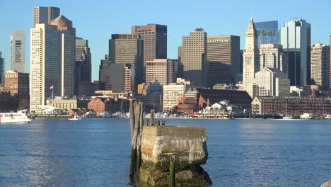 Establishing-shot-of-skyline-of-downtown-Boston-Massachusetts-business-district-with-water-taxis-passing