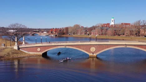Aerial-over-the-John-W-Weeks-Footbridge-reveals-Harvard-University-campus-on-the-Charles-River-with-rowing-crew