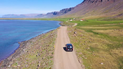 Aerial-over-a-black-van-traveling-on-a-dirt-road-in-Iceland-near-Raudisandur-Beach-in-the-Northwest-Fjords-4